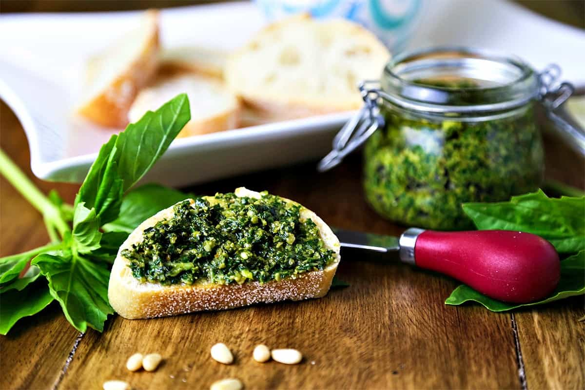 A slice of baguette topped with basil pesto spread on a table