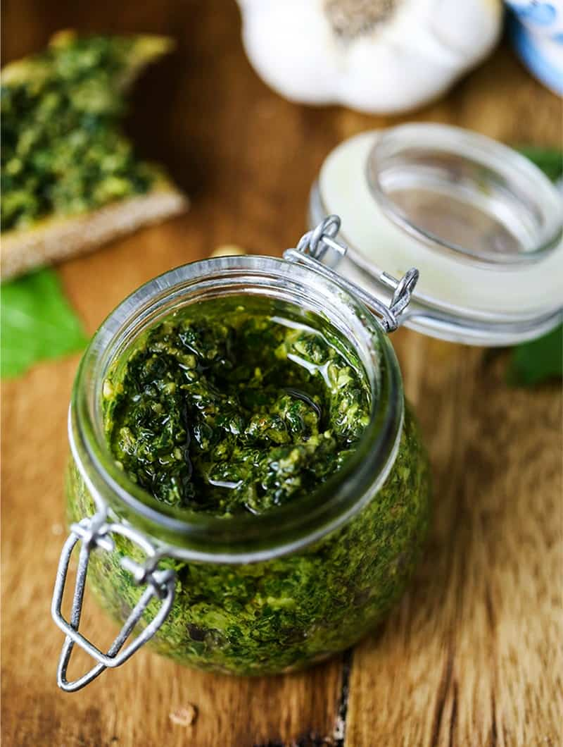 A close up of basil pesto spread in a jar on a table
