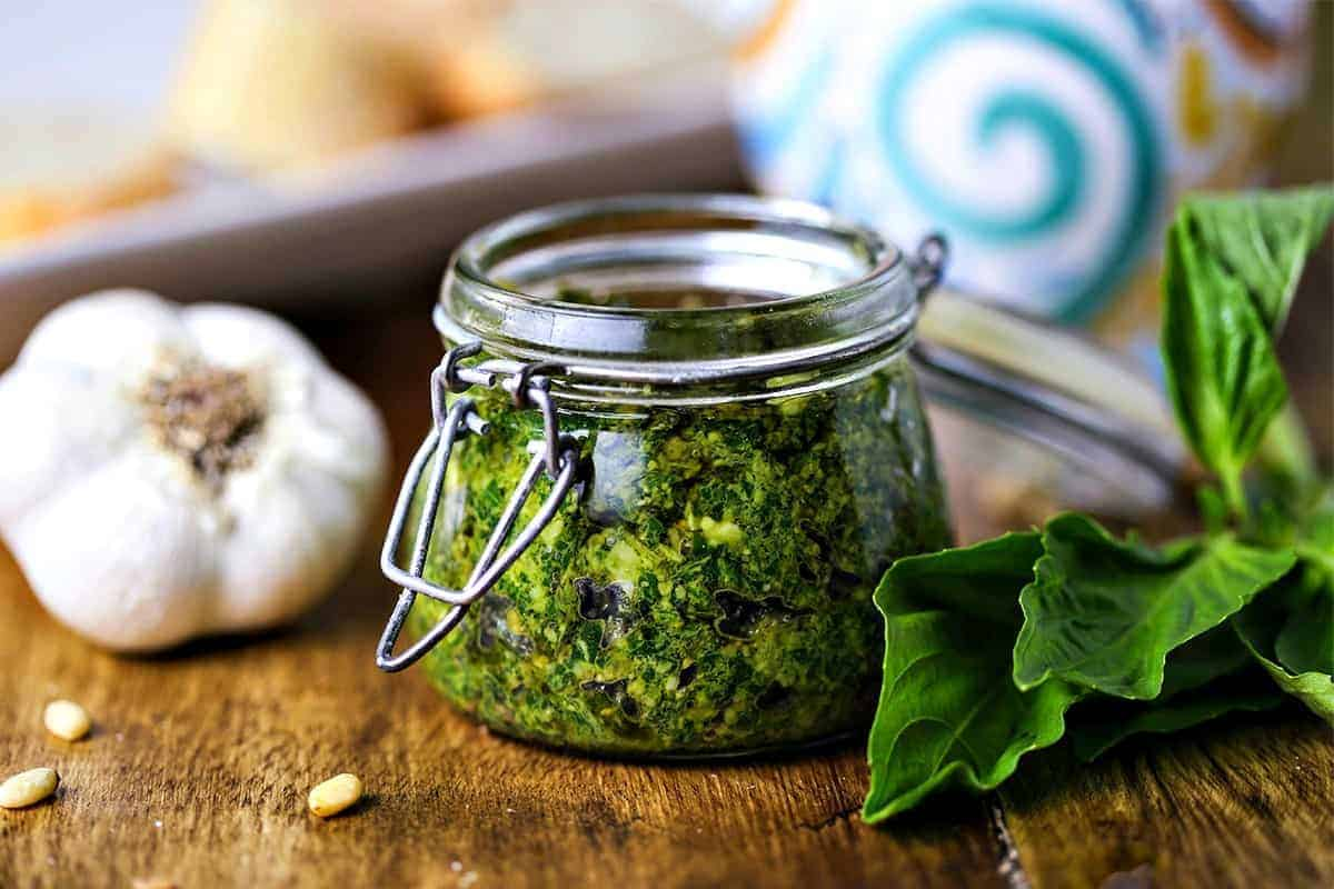 A close up of food on a table, with basil pesto spread