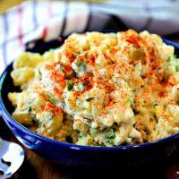 A bowl of fresh herb potato salad on a table.
