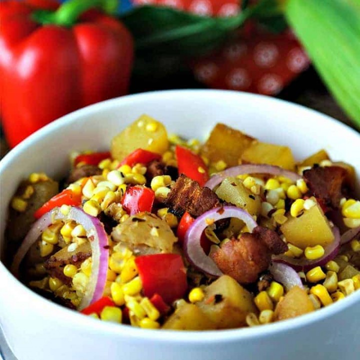 A bowl of food on a plate, with warm corn chowder salad