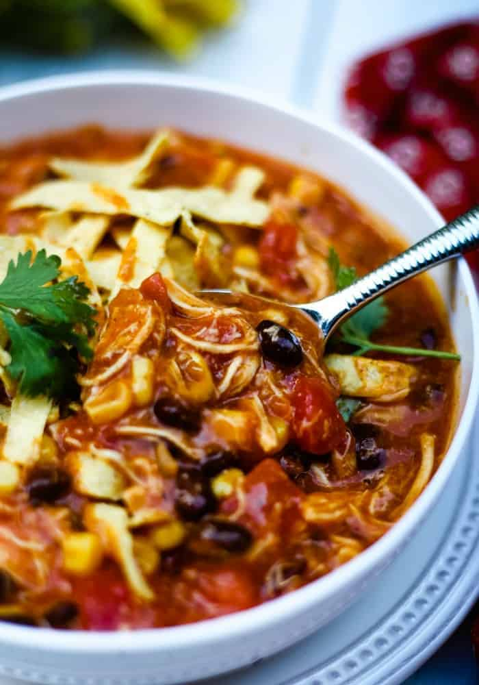 A close up of A bowl of food on a plate, with Chicken Tortilla Soup