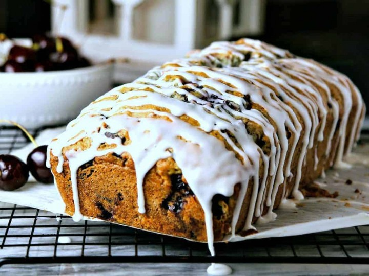 A loaf of cherry chocolate chunk bread with a powdered sugar glaze dripping off the sides