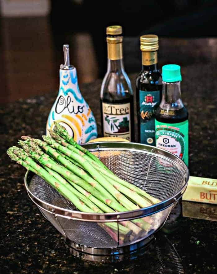 A bottle of balsamic vinegar and a colander of asparagus