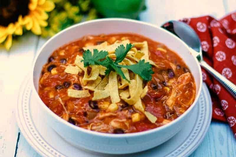 A bowl of food on a plate, with Chicken Tortilla Soup