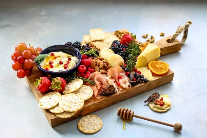 A bunch of food on a cheeseboard, with fruit, berries, and nuts
