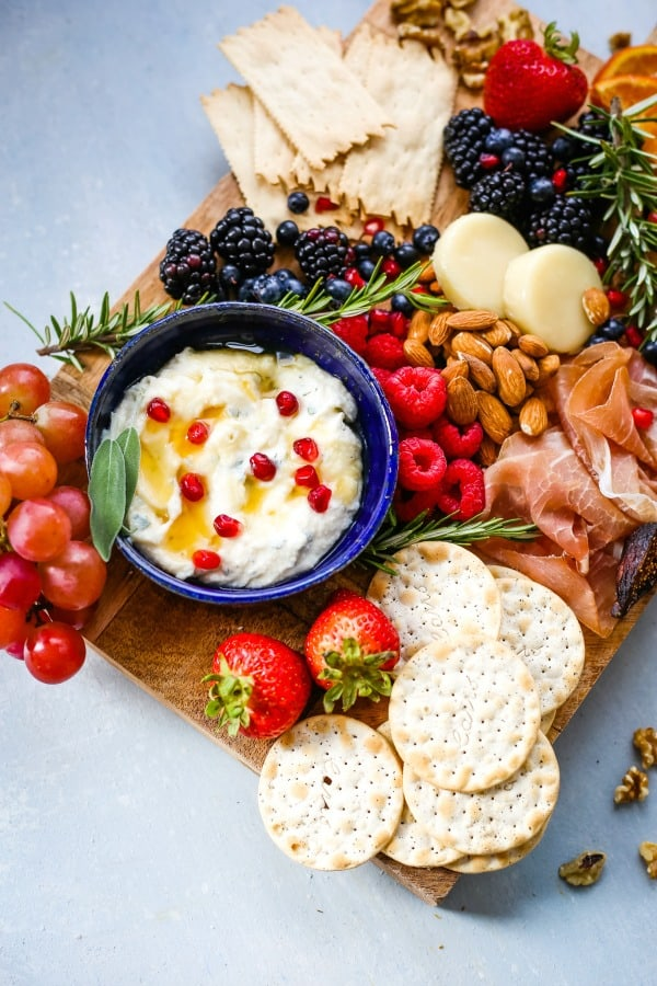 A plate of food on a table, with Cheese, fruit, and crackers