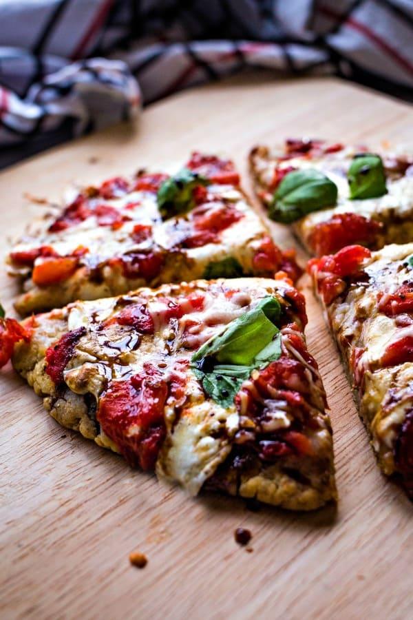 Mini caorese pizza cut into slices on a pizza board