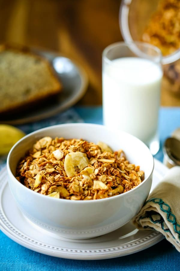 A bowl of peanut butter granola with a glass of milk