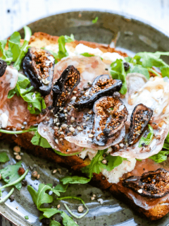A plate of food with a slice of toast, with Ricotta cheese, figs, and arugula