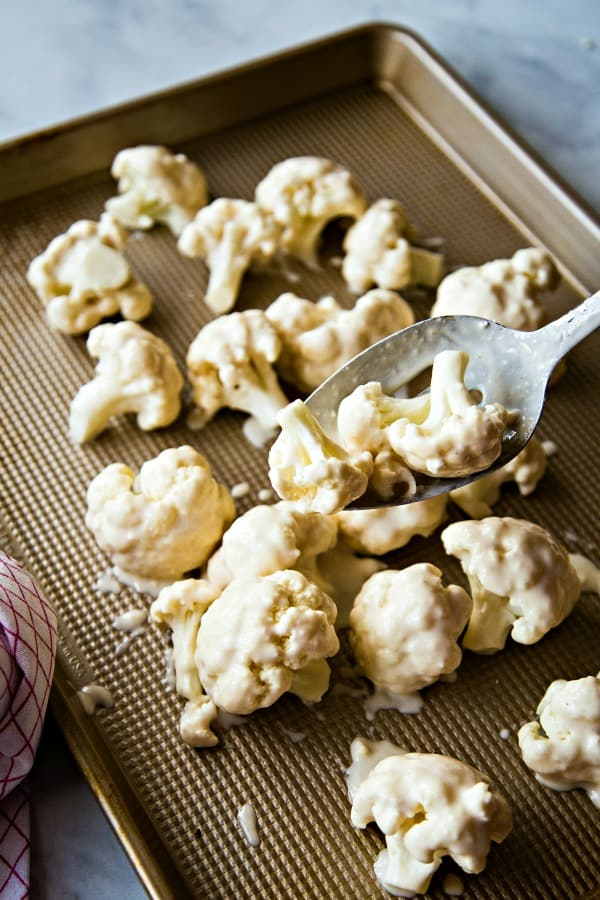Coated cauliflower on baking sheet