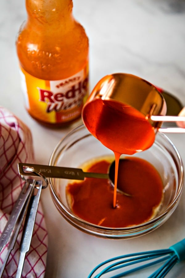 Adding buffalo wing sauce to melted butter