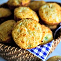 a basket lined with a purple gingham napkin with Mexican cornbread muffins