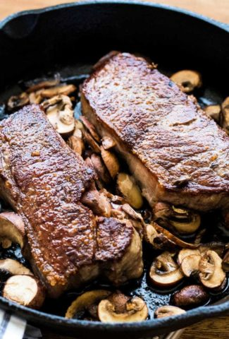 two New York strip steaks with mushrooms in a cast iron skillet