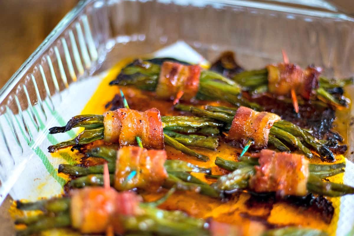 cooked green bean bundles wrapped in bacon in glass dish