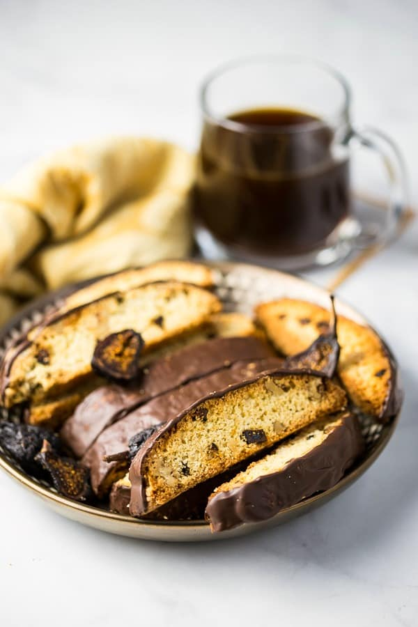 Fig and Walnut Biscotti with Dark Chocolate on gold plate with cup of coffee
