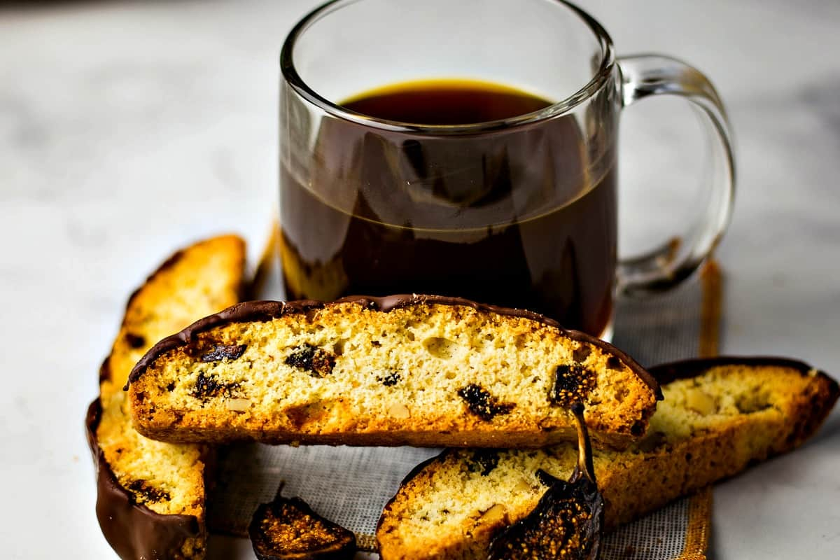 Fig and Walnut Biscotti with Dark Chocolate in front of coffee cup