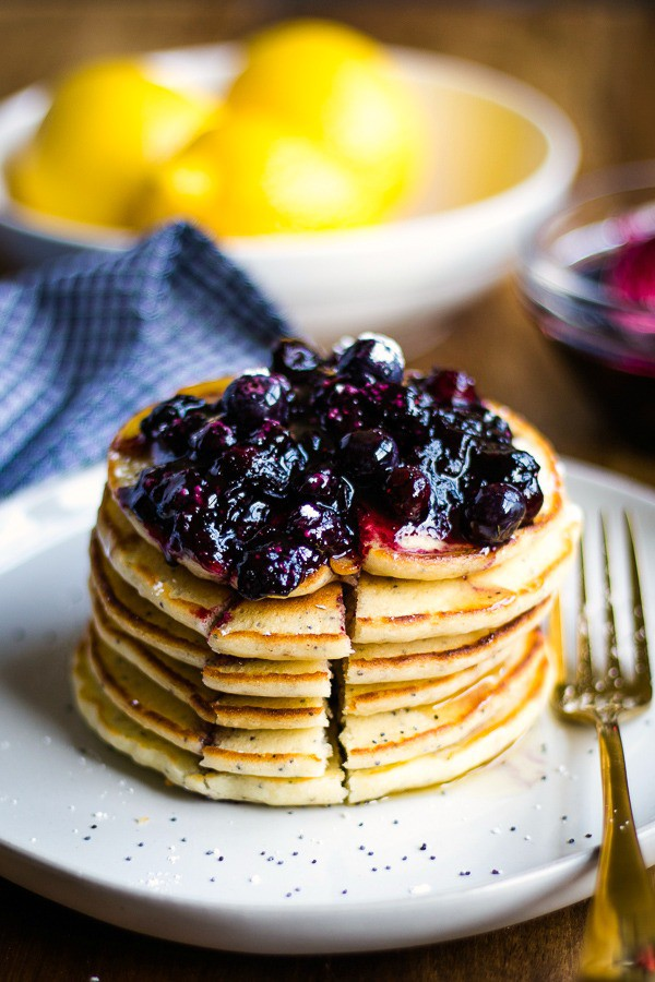 Stack of Lemon Poppy Seed Pancakes with blueberry compote on white plate
