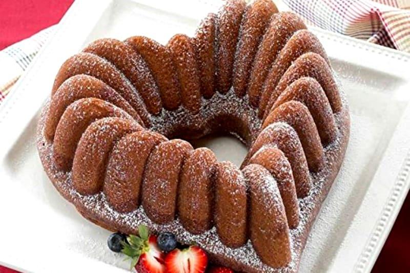 A heart shaped cake on a plate, with Bundt cake pan