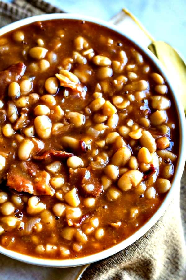 Smoky Chipotle Baked Beans in a white bowl with gold spoon and napkin