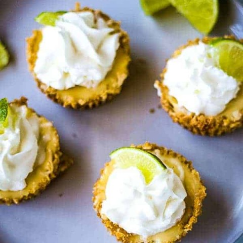 four mini key lime pies on a gray plate with lime garnish