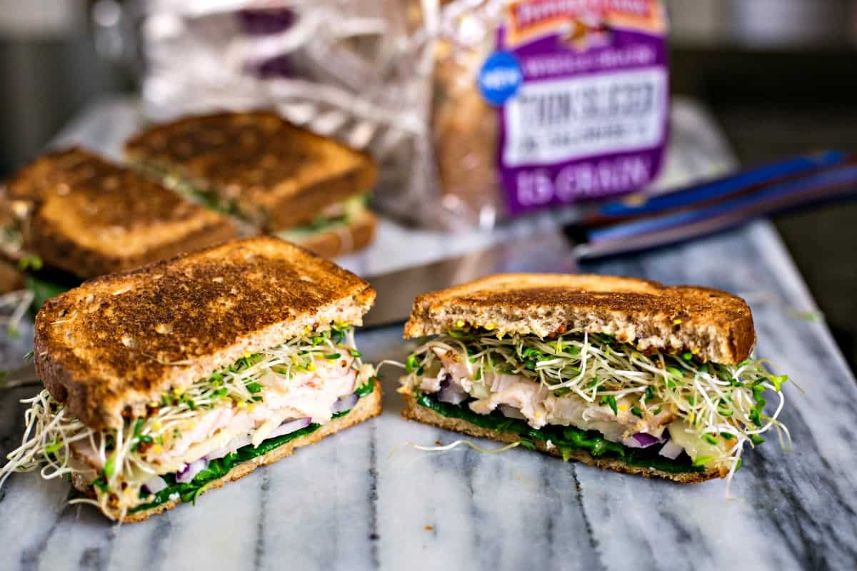 turkey melt sandwiches with alfalfa sprouts cut in half