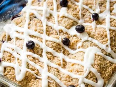 blueberry crumb cake with lemon glaze with fresh blueberry garnish