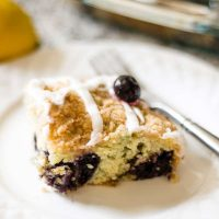 slice of blueberry crumb cake on white plate with fork