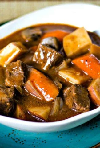 beef stew in a white bowl on a blue plate
