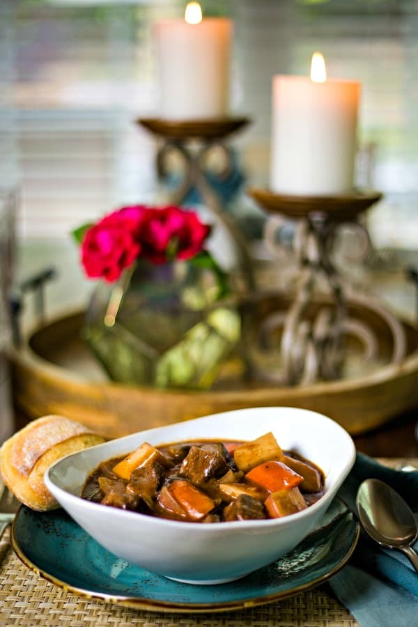 a bowl of beef stew at the dinner table with candles and roses