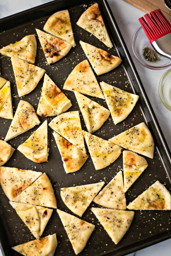 pita bread cut into triangles on a baking sheet