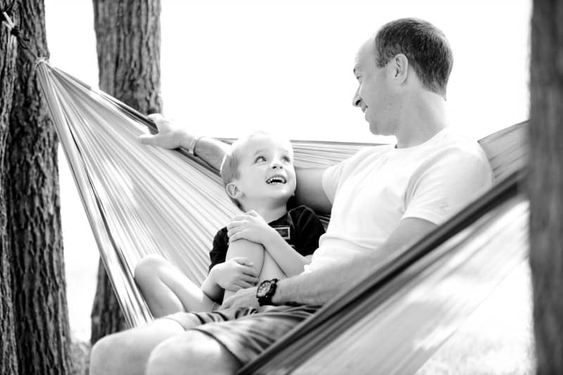 A man and a boy sitting in a hammock