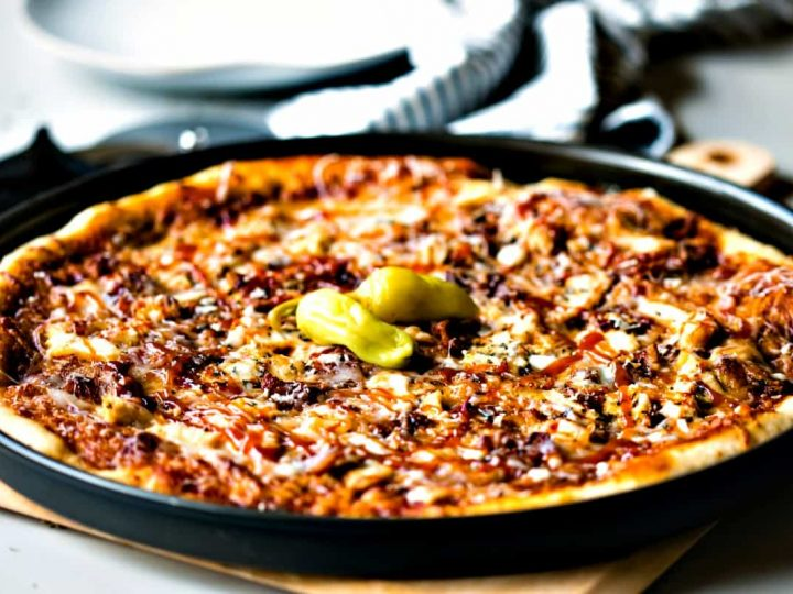 Barbecue Chicken Pizza in a black pizza pan garnished with pepperoncini