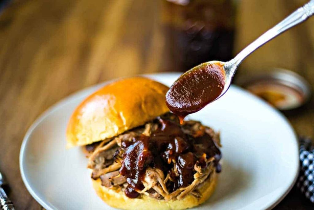 A plate of food and a spoon on a table, with Barbecue sauce and pulled pork