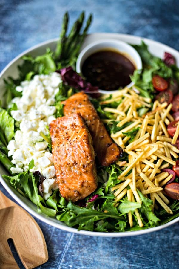 grilled salmon on salad greens in a white bowl on a blue background