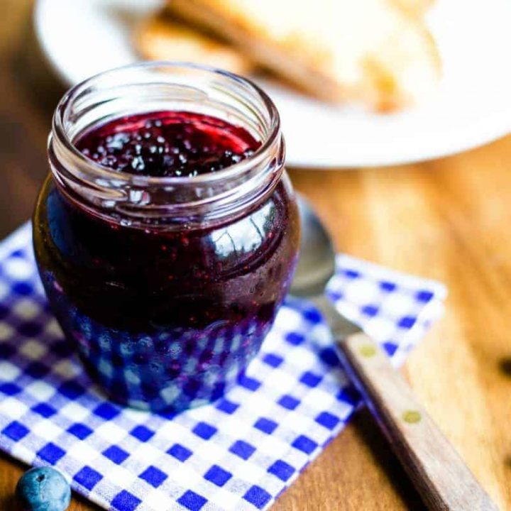 a jar of blueberry jam on a checked napkin