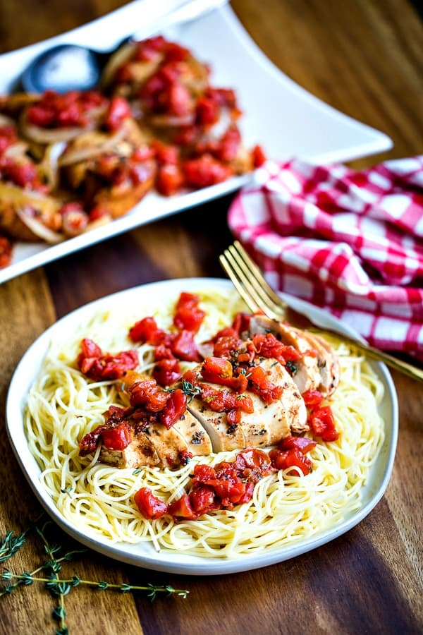 Slow Cooker Balsamic Chicken on bed of angel hair pasta with a checkered napkin
