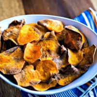 sweet potato chips in a white bowl with a blue and orange napkin