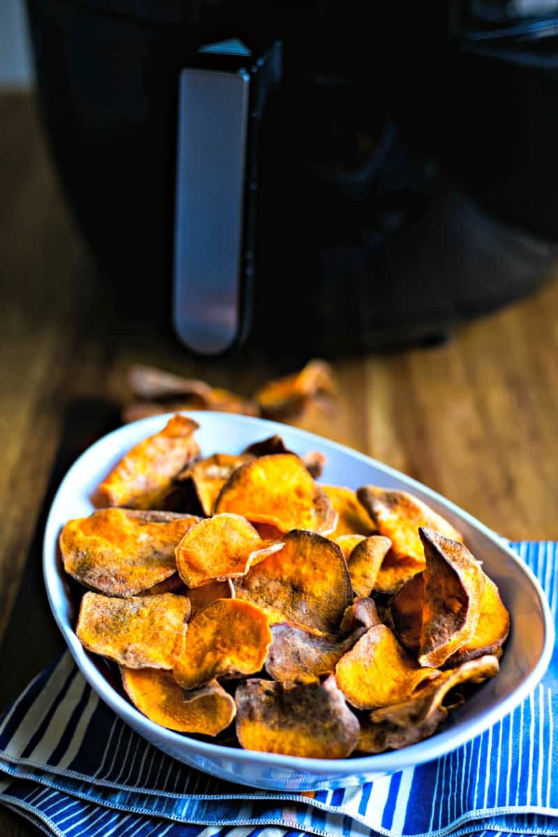 sweet potato chips in a white bowl in front of an air fryer