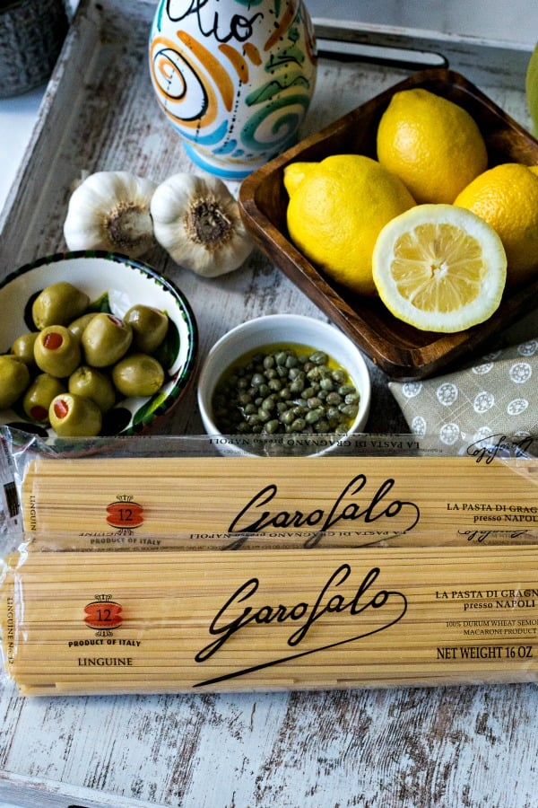 tray with recipe ingredients including pasta, capers, and lemons