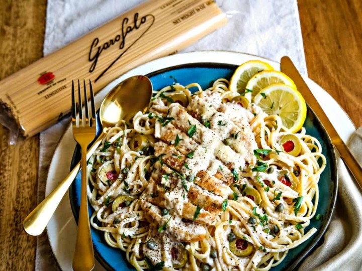 linguini with chicken in a lemon parmesan sauce on a blue plate