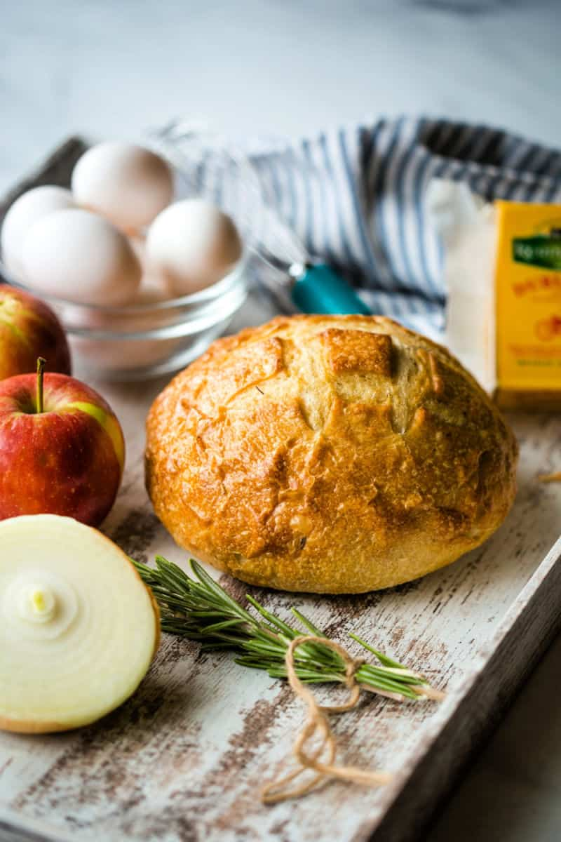 a loaf of sourdough bread on a tray with fresh rosemary, a bowl of eggs, apples, and a block of cheese