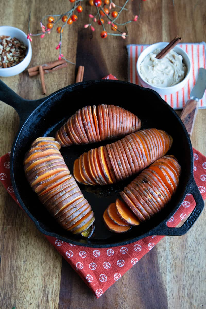 sweet potatoes in a cast iron skillet on wooden table with a bowl of cinnamon butter