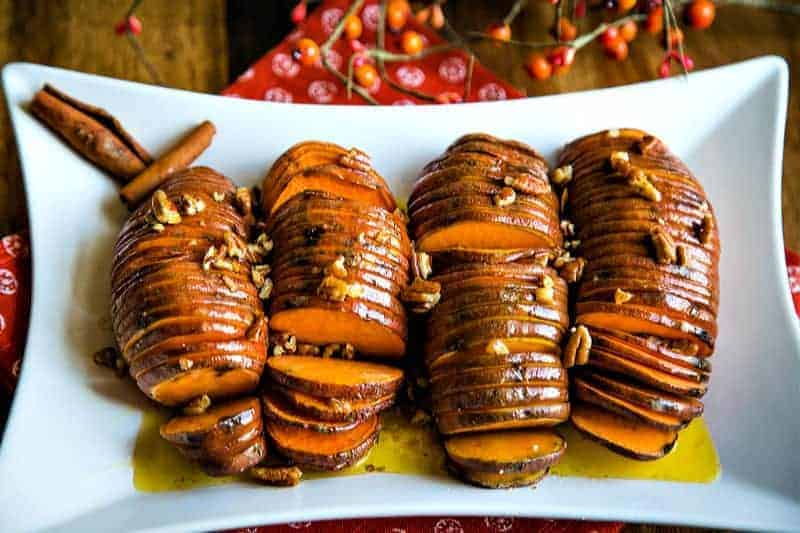 a white platter with four hasselback sweet potatoes drizzled in melted butter and pecans