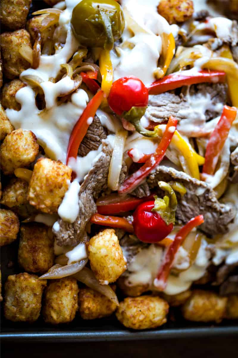 A dish is filled with food, with Cheesesteak, tater tots, and cheese