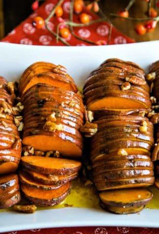 hasselback sweet potatoes on a white platter with cinnamon stick garnish