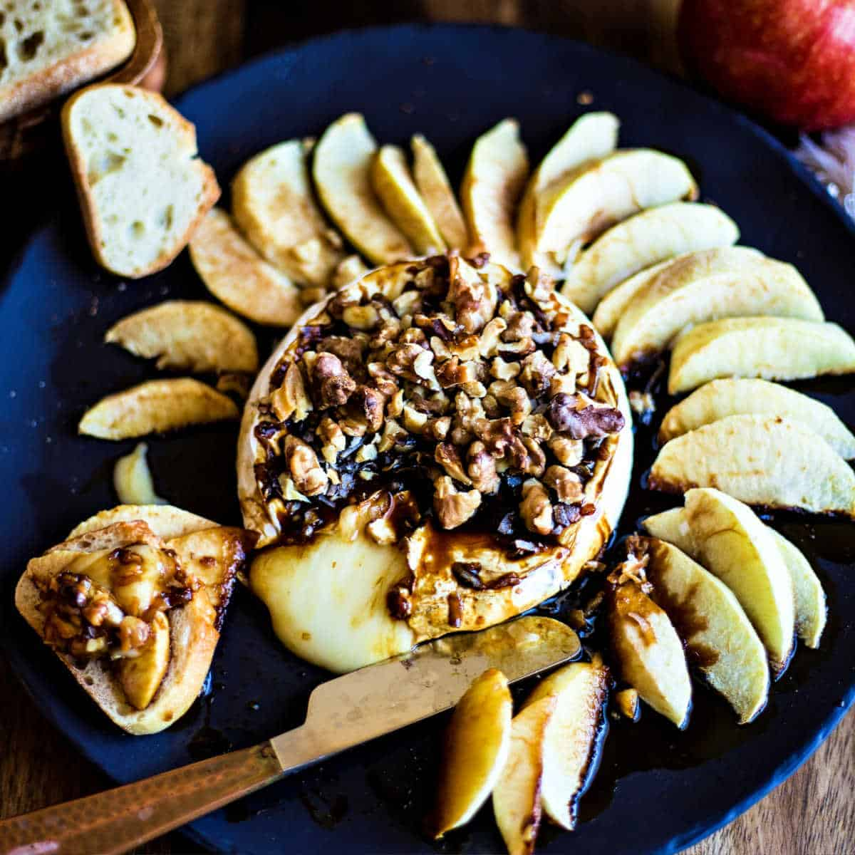 baked brie on a slate platter with apple slices, molasses, and walnuts with the cheese ozzing
