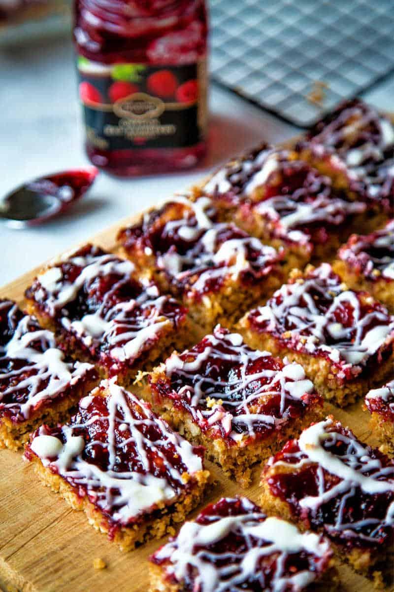 sliced raspberry oatmeal bars on a wooden cutting board
