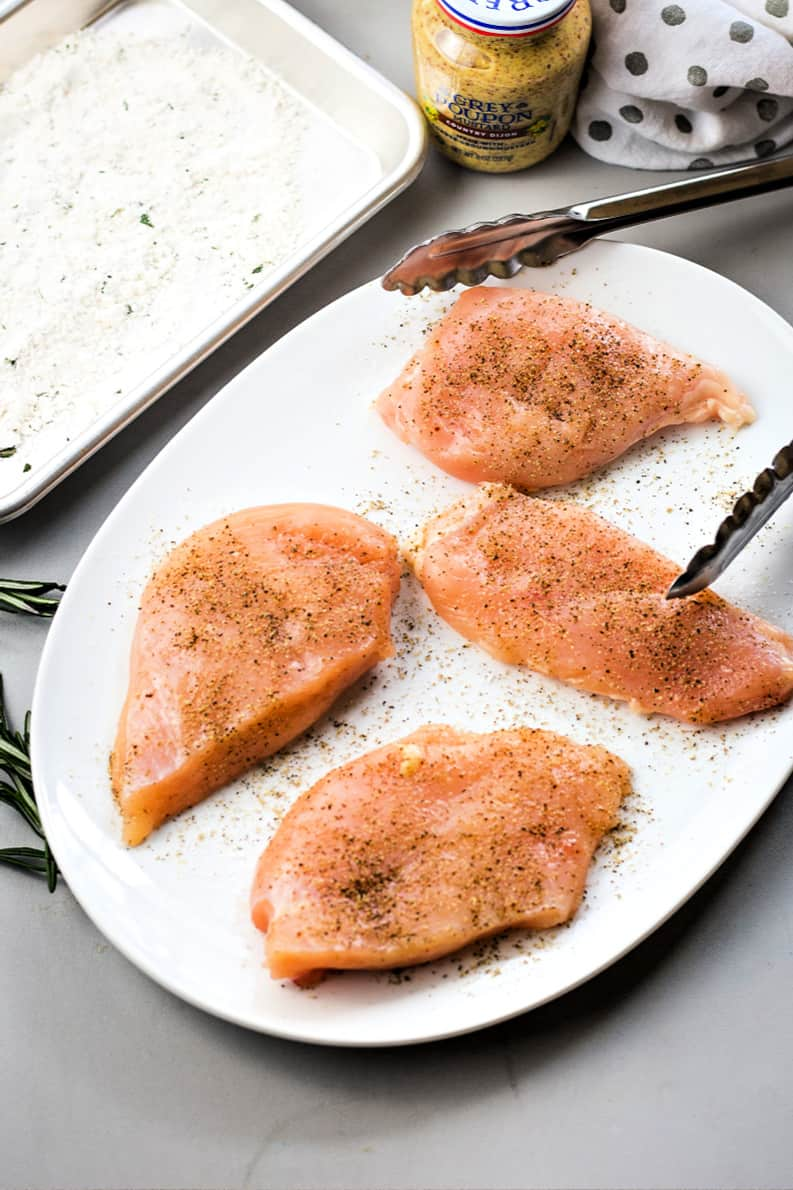 raw chicken breasts on a white platter seasoned with salt and pepper