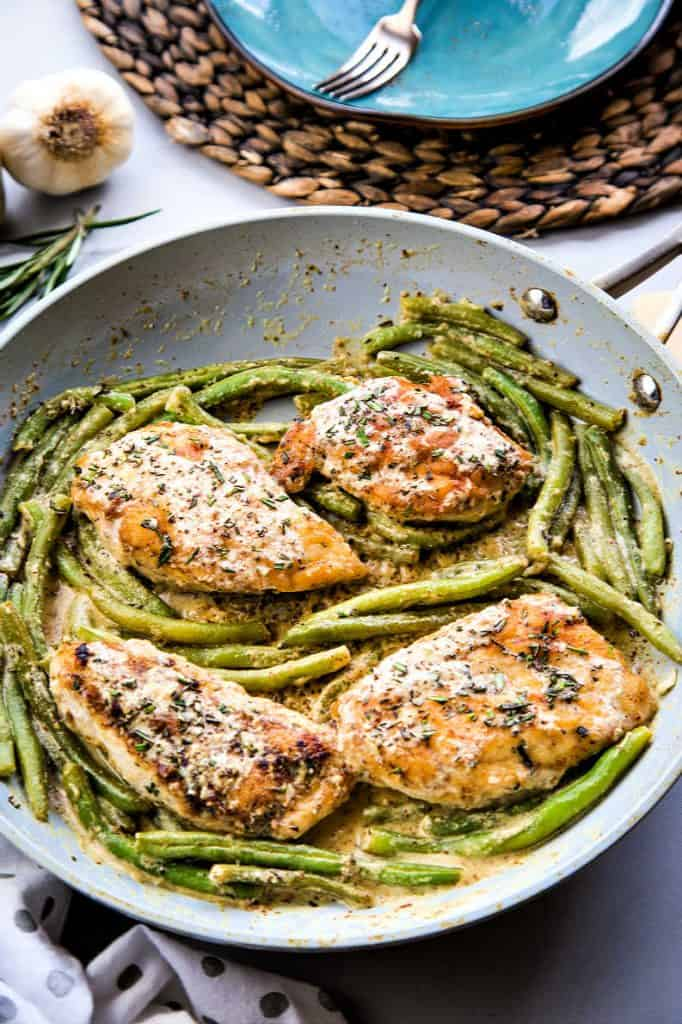 a fry pan with chicken and green beans on a table ready to serve